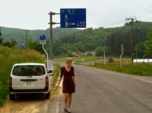Jessica touring an evacuated section of Fukushima prefecture in June, 2013. She stopped to look at a soil decontamination project that was occurring in a rice field near the road. The mask was worn for protection against radioactive dust particles.